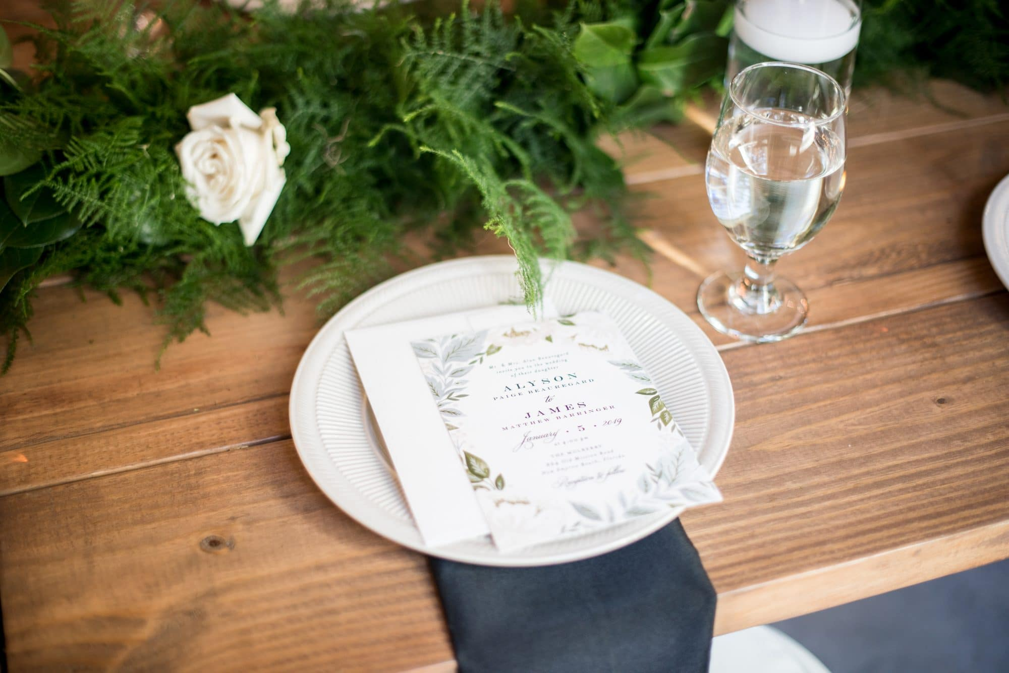 The Magnolia Company - Reception table place setting with greenery centerpiece
