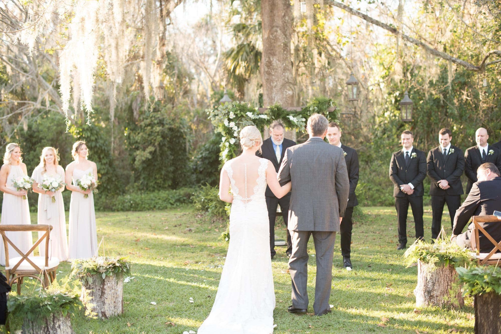 The Magnolia Company - outdoor wedding ceremony under greenery-draped arch