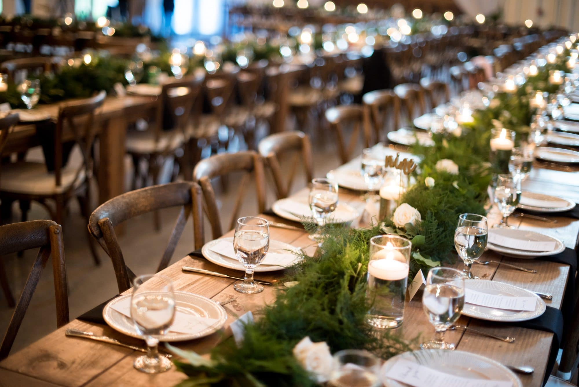 The Magnolia Company - long rustic reception table with magnolia/greenery runner