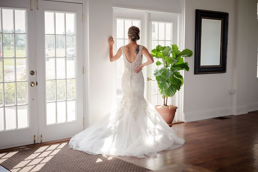 Bella-Cosa-Lakeside-Bride standing in the sunrays staring out of french doors