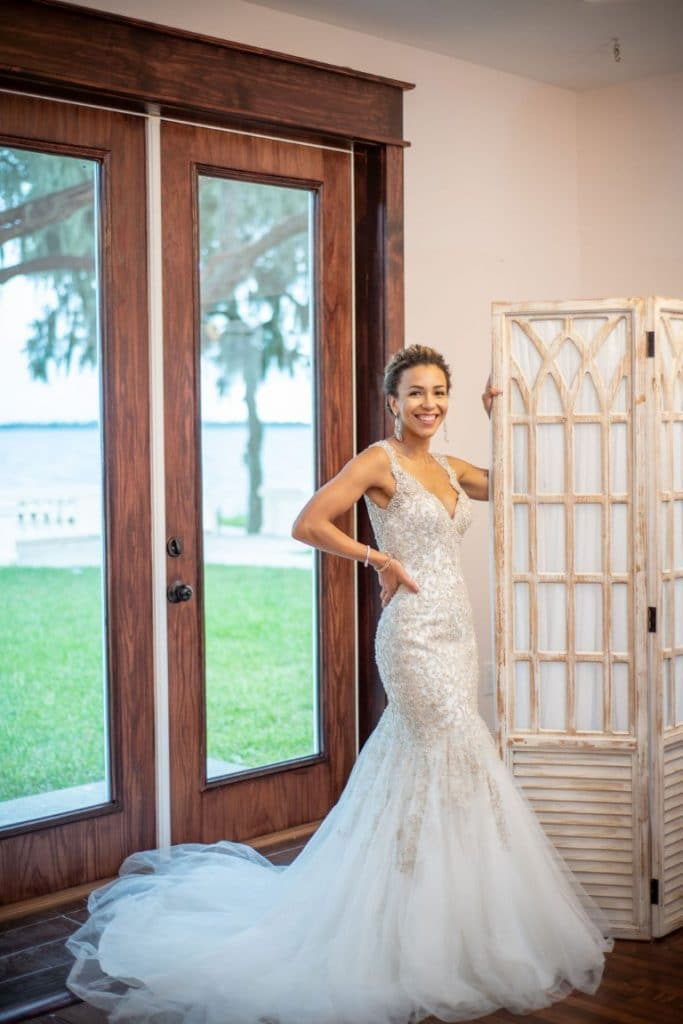 Bella-Cosa-Lakeside-Bride smiling next to large picture window doors and changing wall