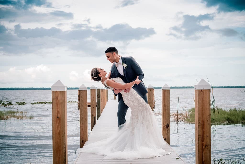Bella-Cosa-Lakeside-Groom dipping wife on dock by lake