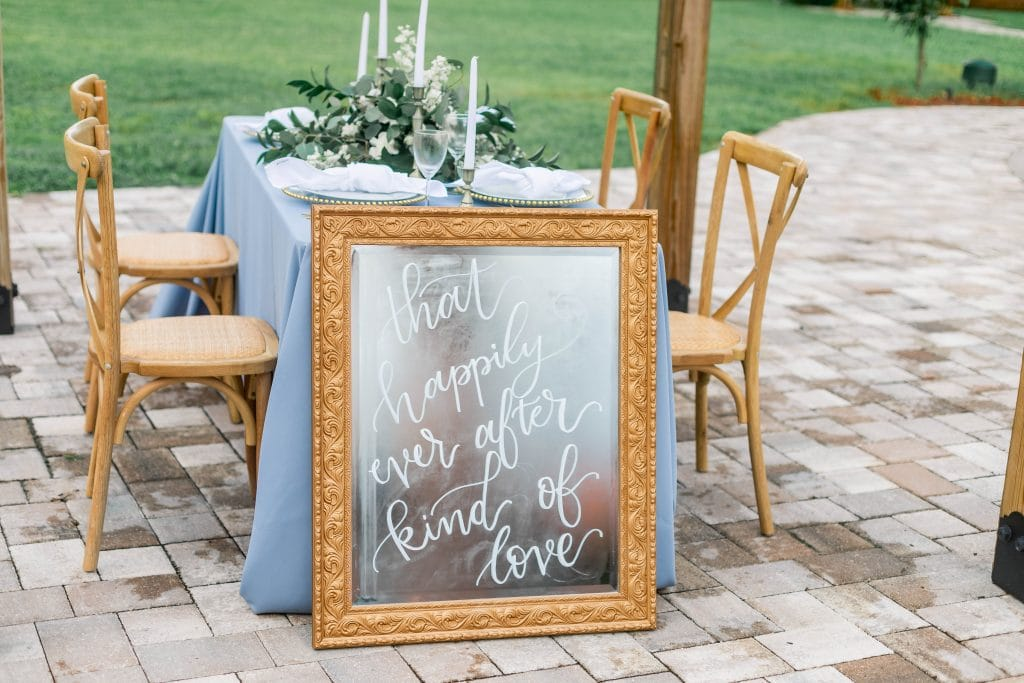 Idlewood Wedding Venue wedding reception table setup outside near pool with hand drawn sign