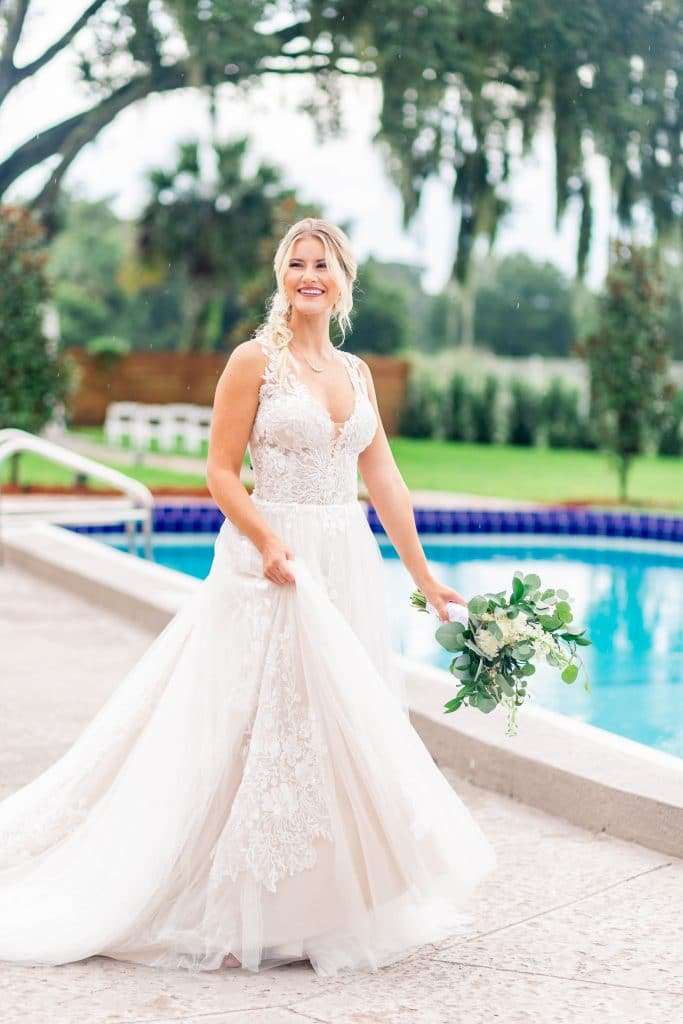 Idlewood Wedding Venue bride smiling outside near pool holding bouquet of flowers
