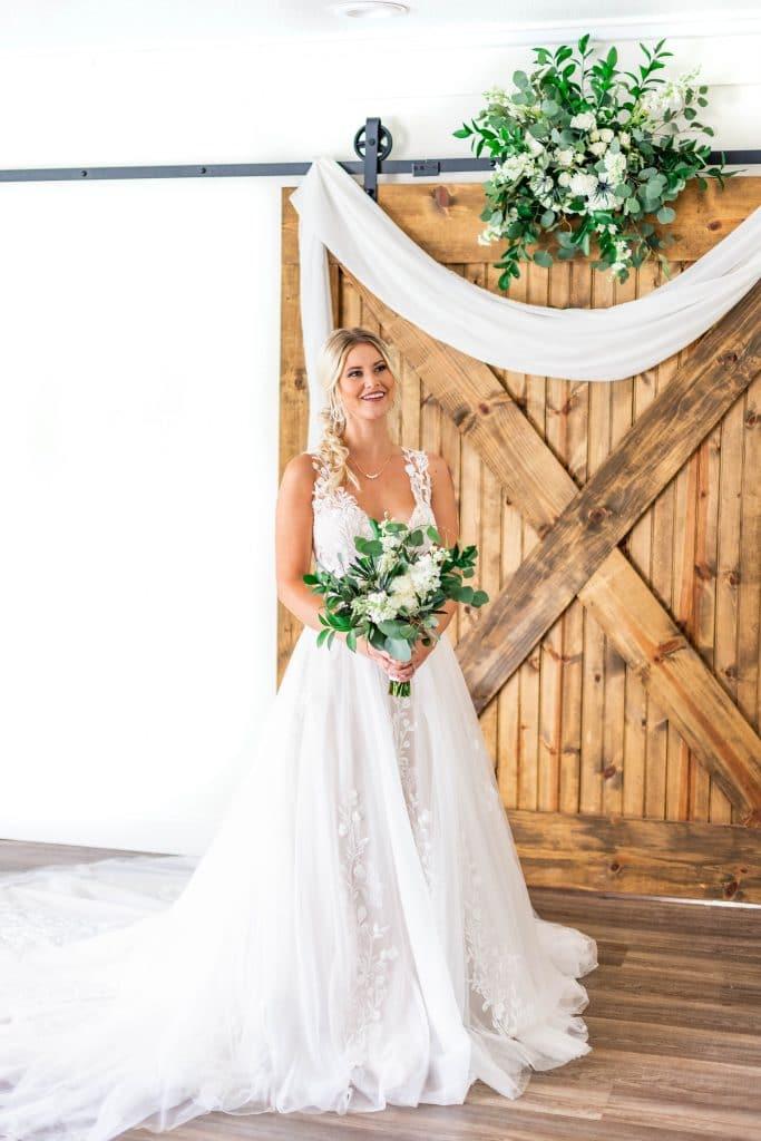 Idlewood Wedding Venue bride standing in front of decorated barn doors