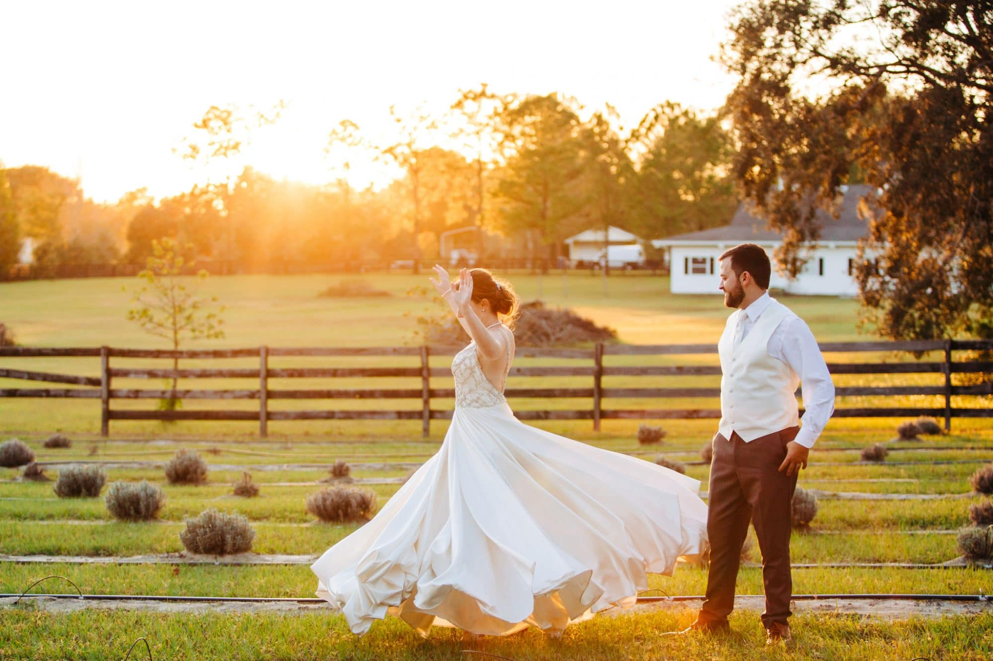 Live Love Laugh Events - groom watching bride twirl in open field