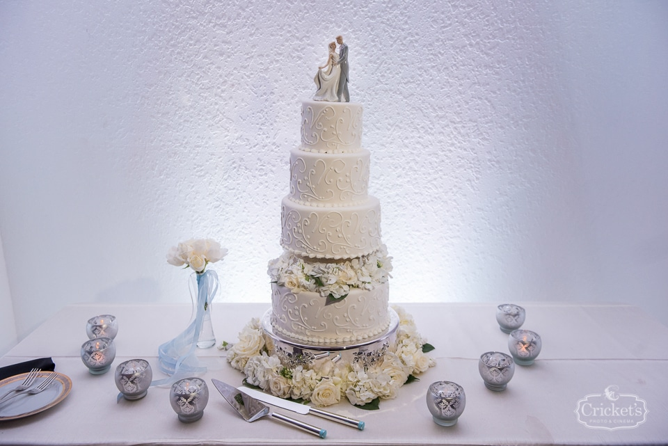 Sofelle Cake Artistry - white filigree wedding cake on table