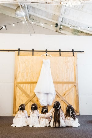 1010 West - flower girls on floor gazing up at wedding dress hung on wall