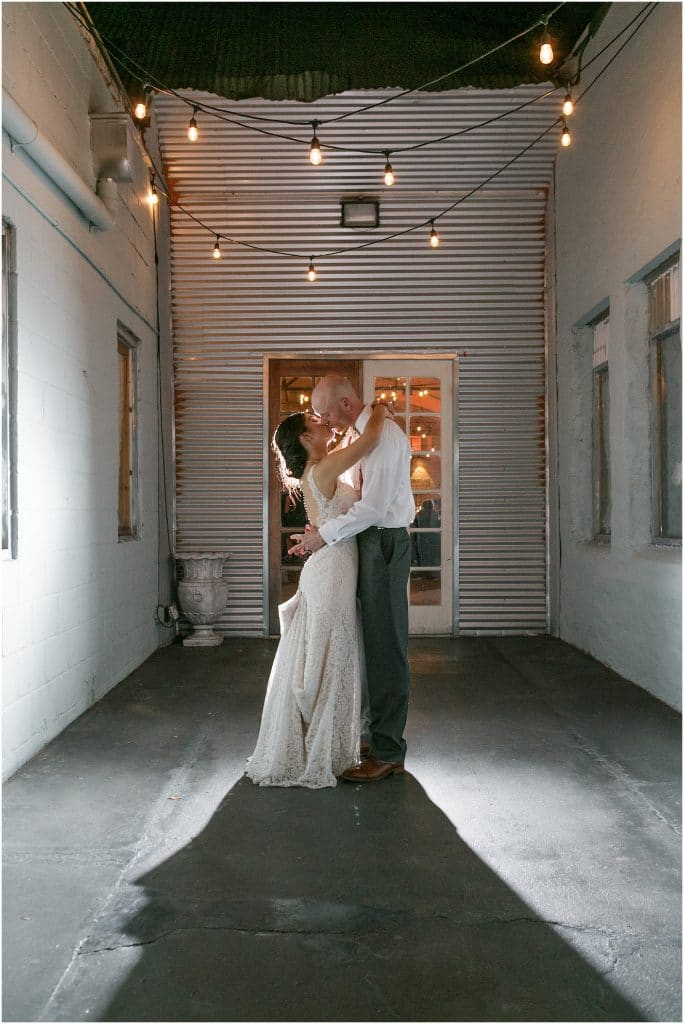 1010 West - bride and groom kissing in front of corrugated iron wall