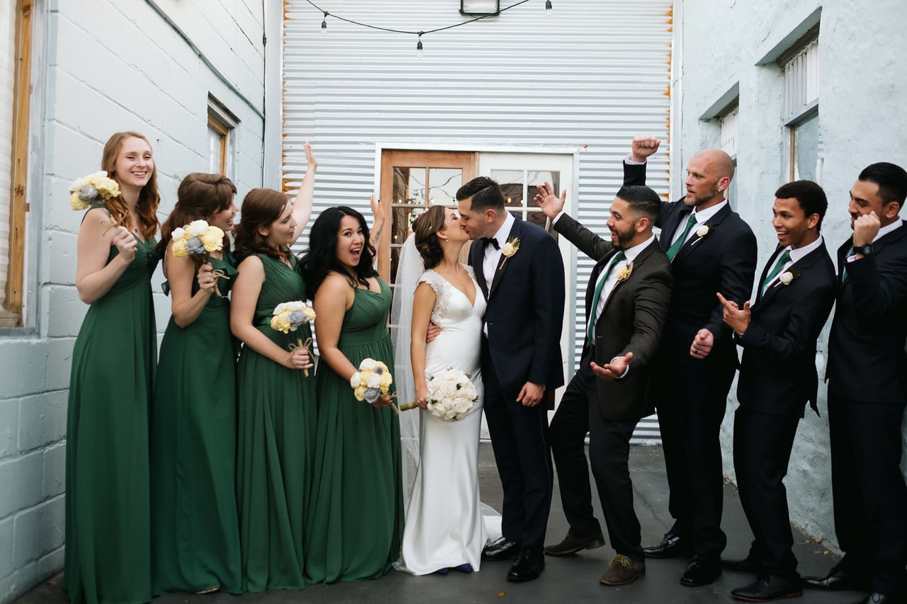 1010 West - bride and groom kissing while wedding party celebrates around them