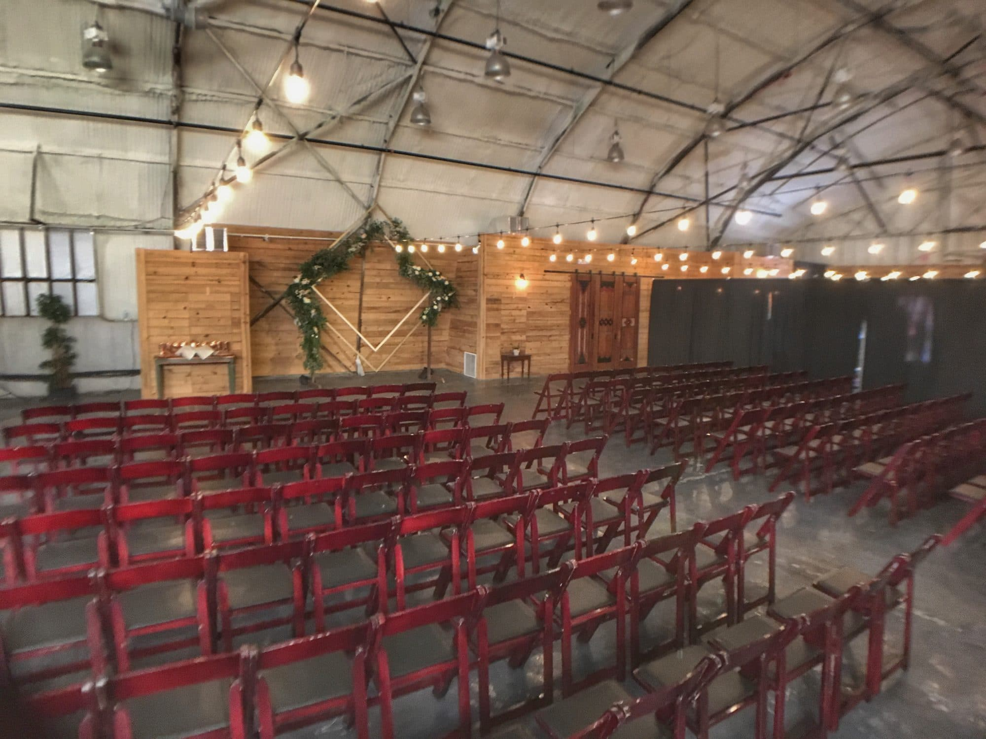 1010 West - rustic pallet wall backdrop to wedding venue inside hangar