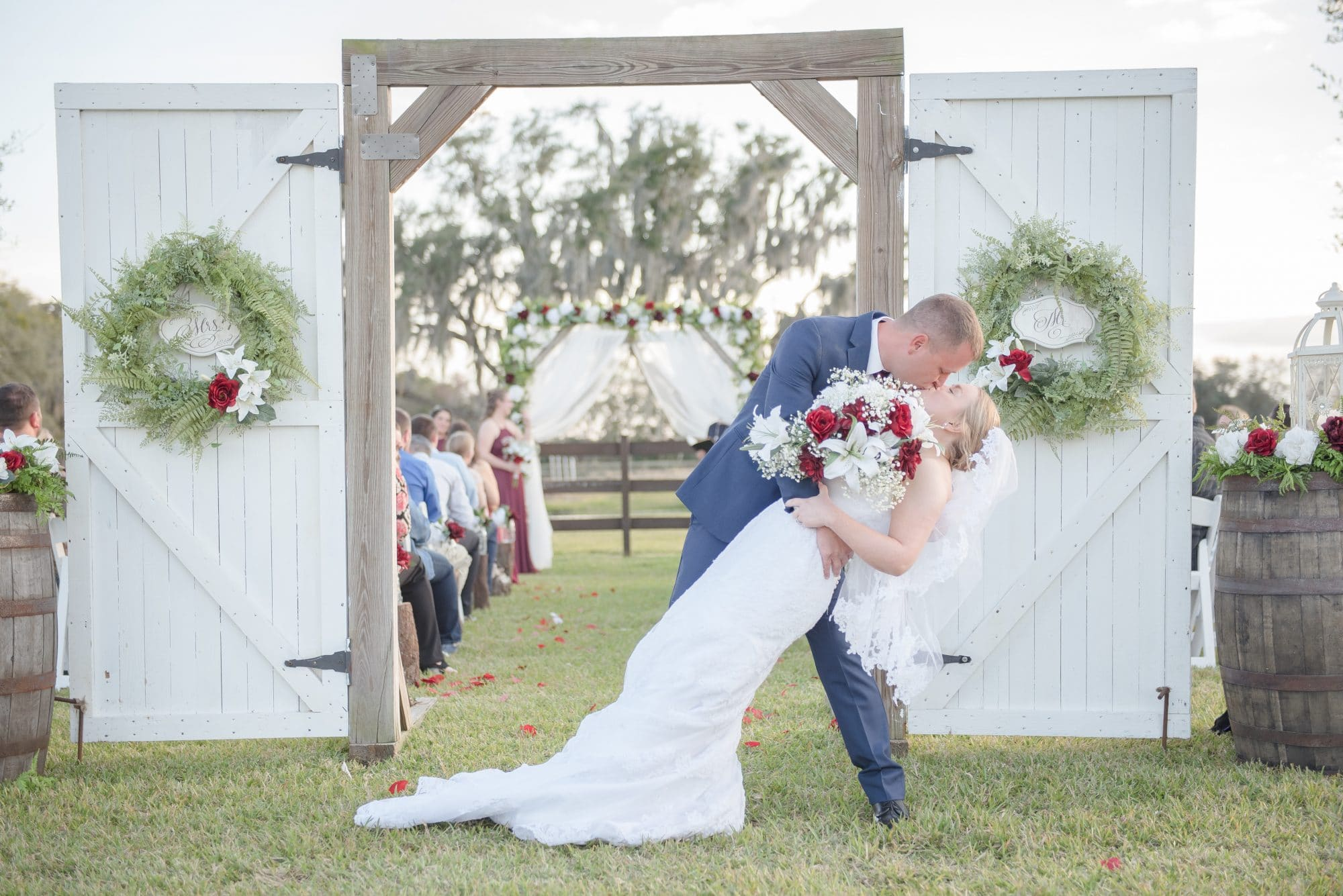 Todd dipping Brittany for a kiss in front of rustic freestanding door