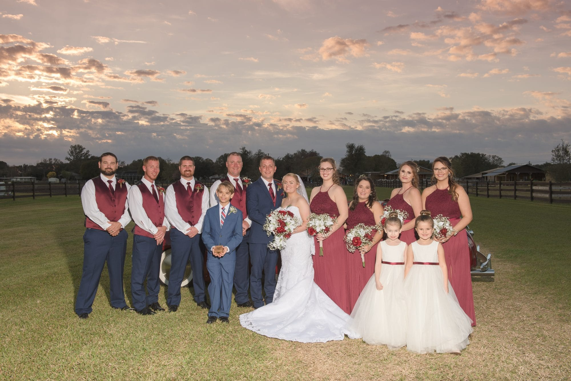 Bride and groom with wedding party in field at sunset.