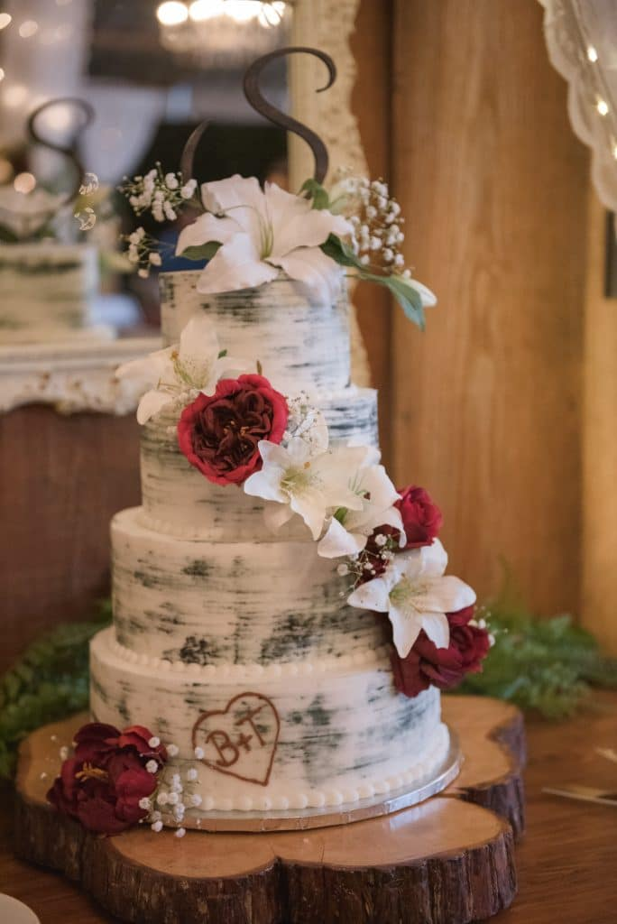 Semi-naked wedding cake with couples' initials in a heart