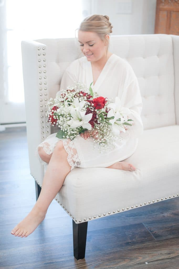 Bride Brittany sitting on couch in white robe holding a bouquet