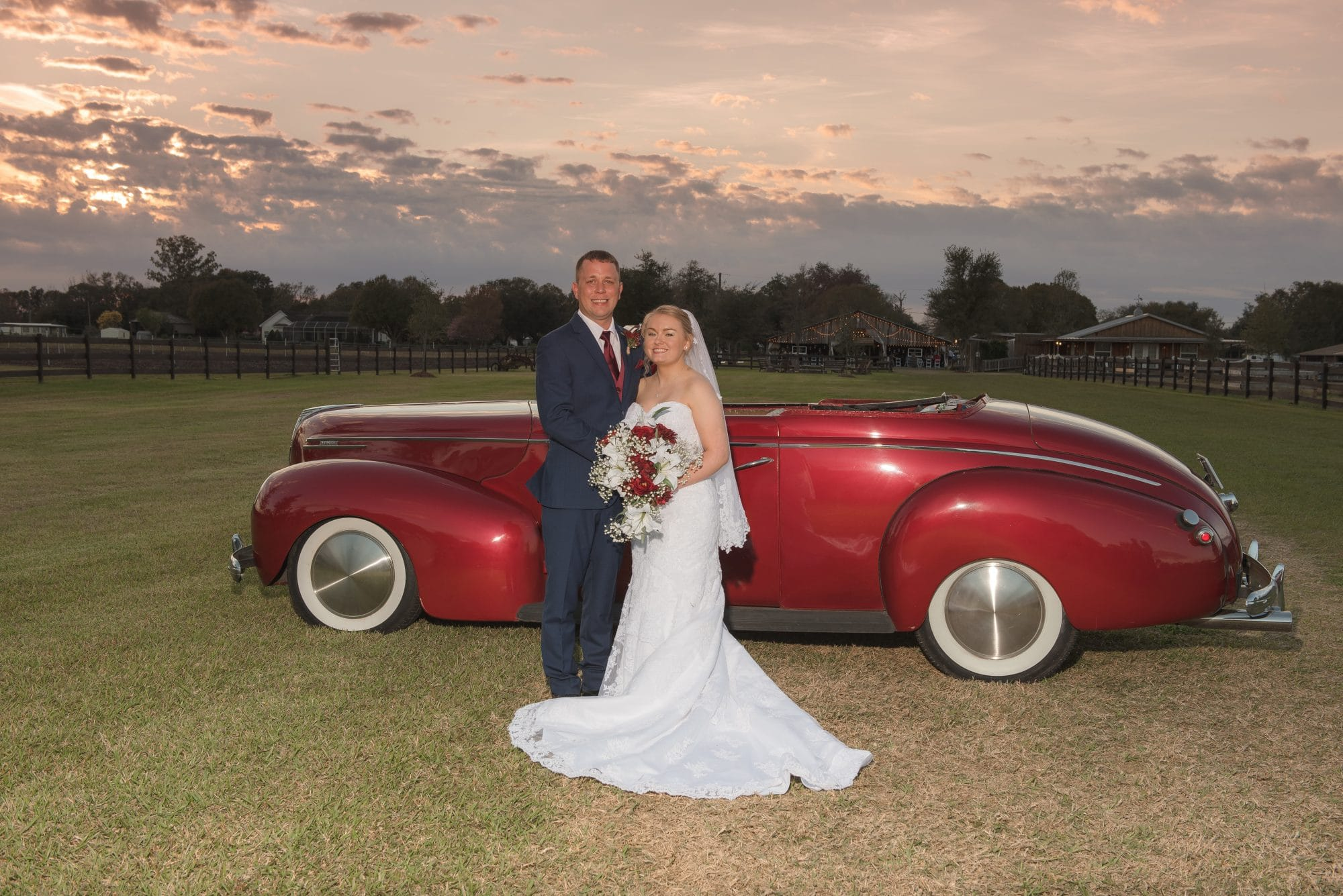 Bride and groom next to red vintage car.