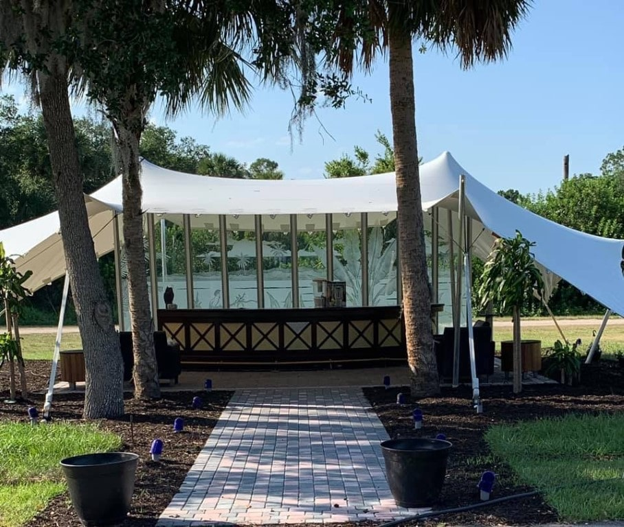Cedar-Knoll-Events-FL-White tented area with paver walkway lined with tall trees