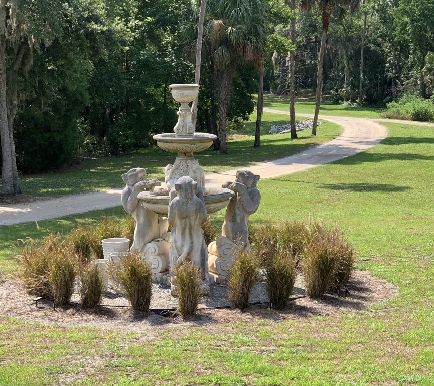 Cedar-Knoll-Events-FL-Stone fountain with panthers standing on hind legs with small bushes surrounding it