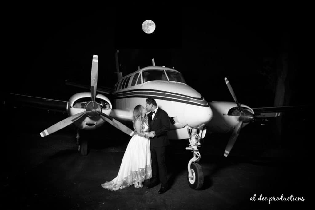 Cedar-Knoll-Events-FL-Couple kissing in front of small prop plane