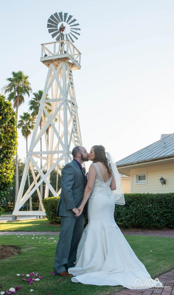 Celebration Golf Club - newlyweds kissing with windmill behind them