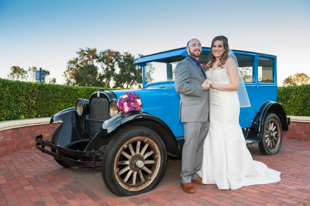 Celebration-Golf-Club-Happy couple holding hands standing in front of antique blue car