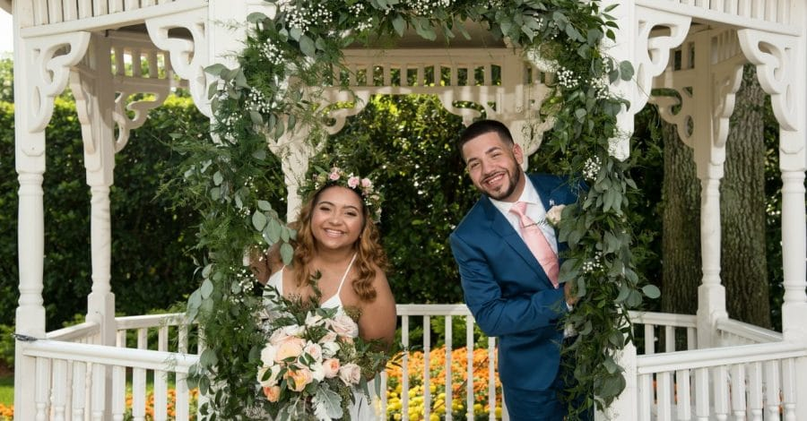 Celebration-Golf-Club-Bride and Groom peaking around gazebo opening with greenery arch around them