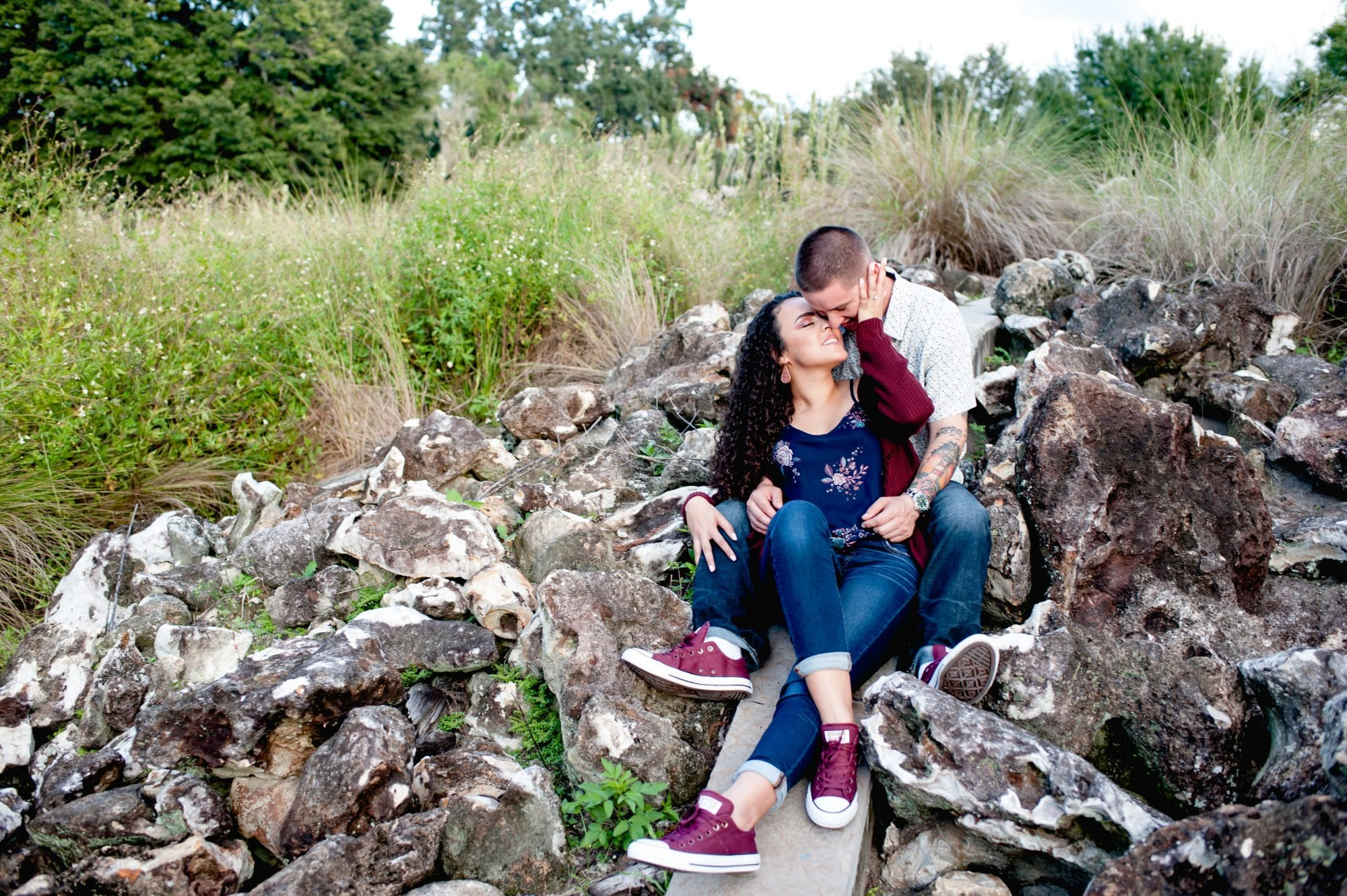 Embrace by Kara - engagement shoot of couple on rock hill in matching burgundy sneakers