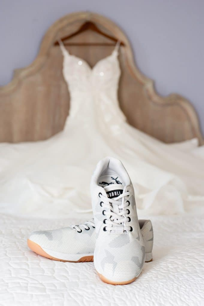 Embrace by Kara - bridal sneakers on bed with wedding dress hung up in background
