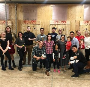 Epic-Axe-Throwing-group holding axes in front of target boards