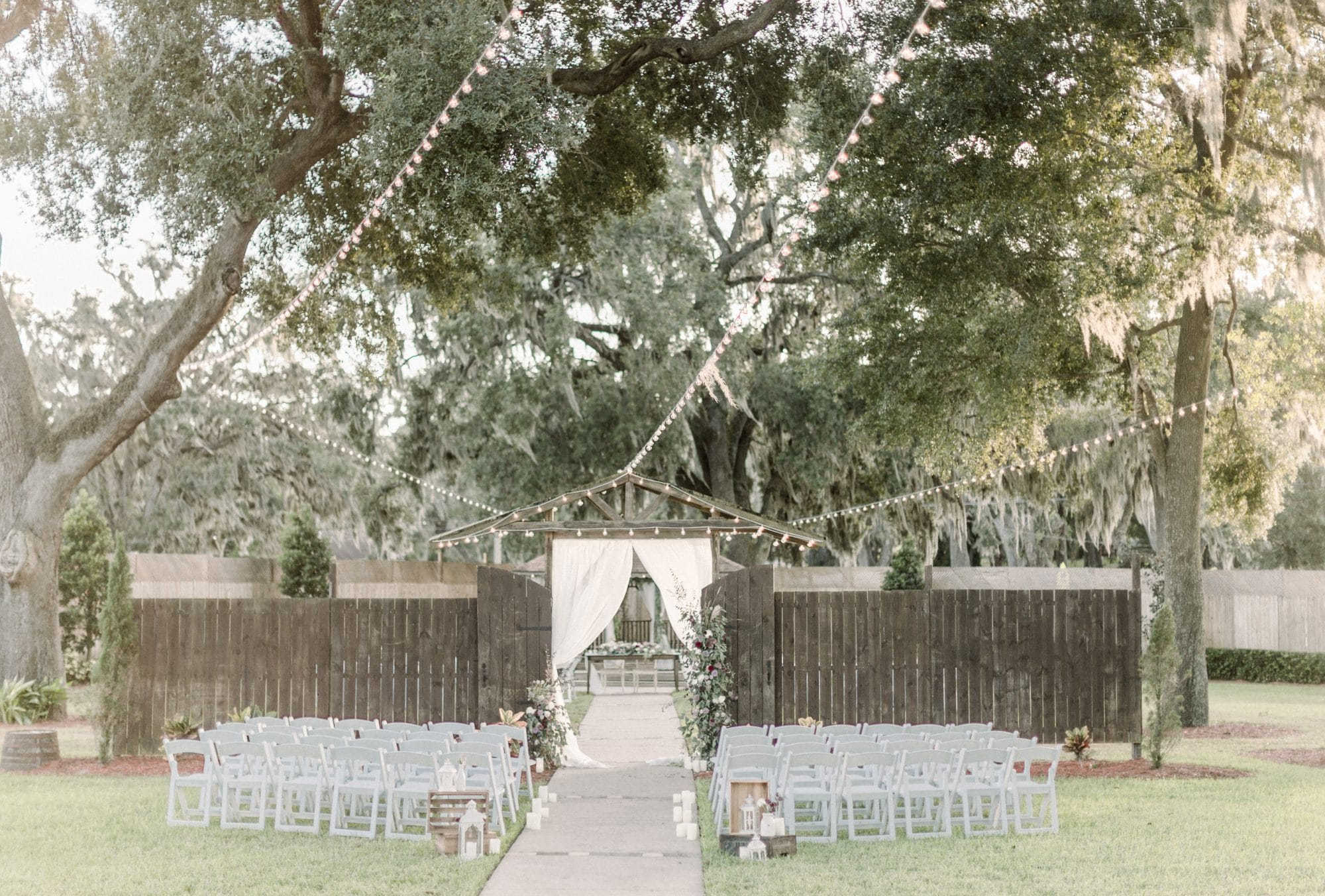 Harmony Haven Event Venue - rustic outdoor ceremony space with market lighting and rustic wooden backdrop