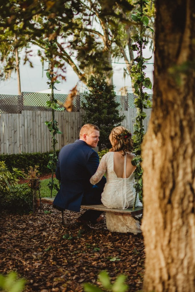 Harmony Haven Event Venue - bride and groom on rustic tree swing covered with vines