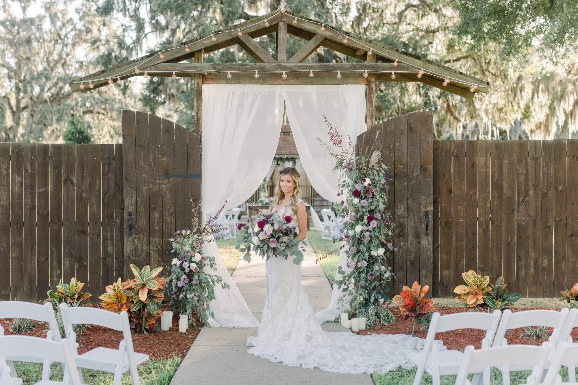 Harmony Haven Event Venue - bride standing under rustic wooden archway draped with curtains