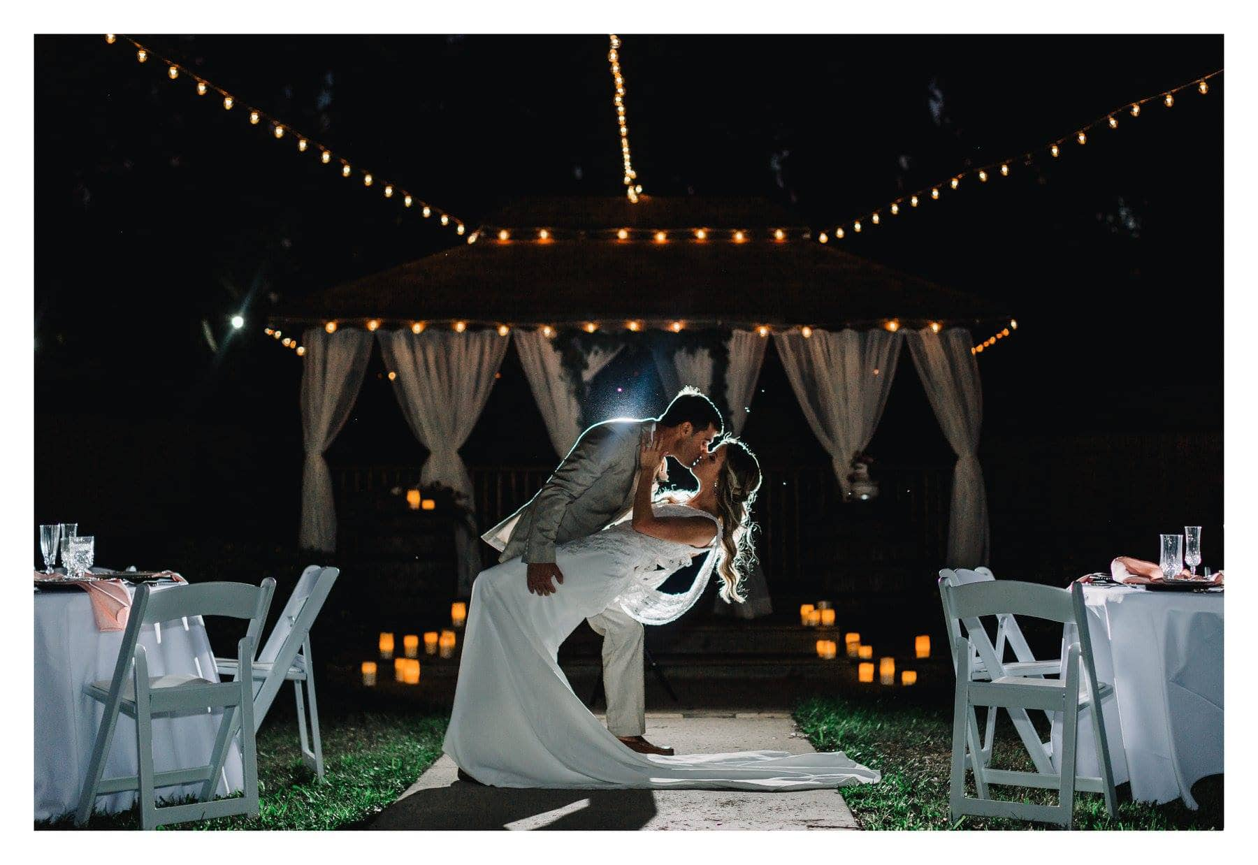 Harmony Haven Event Venue - groom dipping bride for a kiss at beautiful nighttime reception.