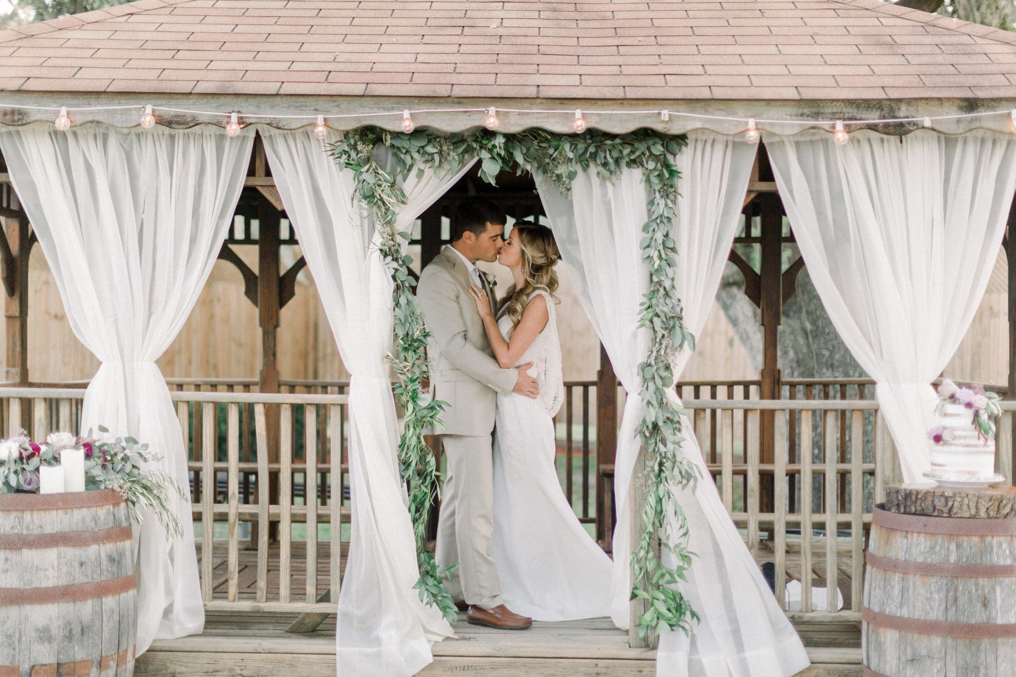 Harmony Haven Event Venue - newlyweds kissing under gazebo draped with curtains and eucalyptus