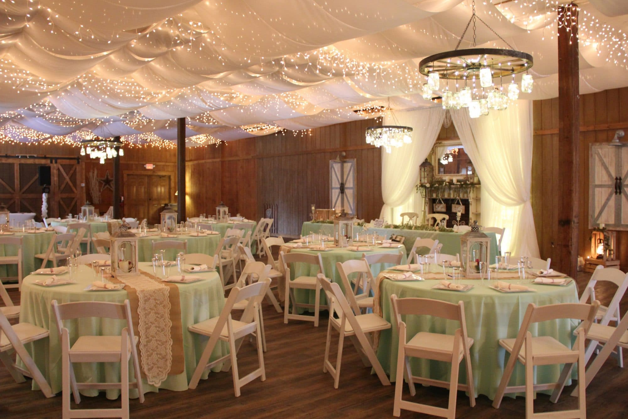 Harmony Haven Event Venue - wedding reception venue with white fabric draping and icicle lights on the ceiling.