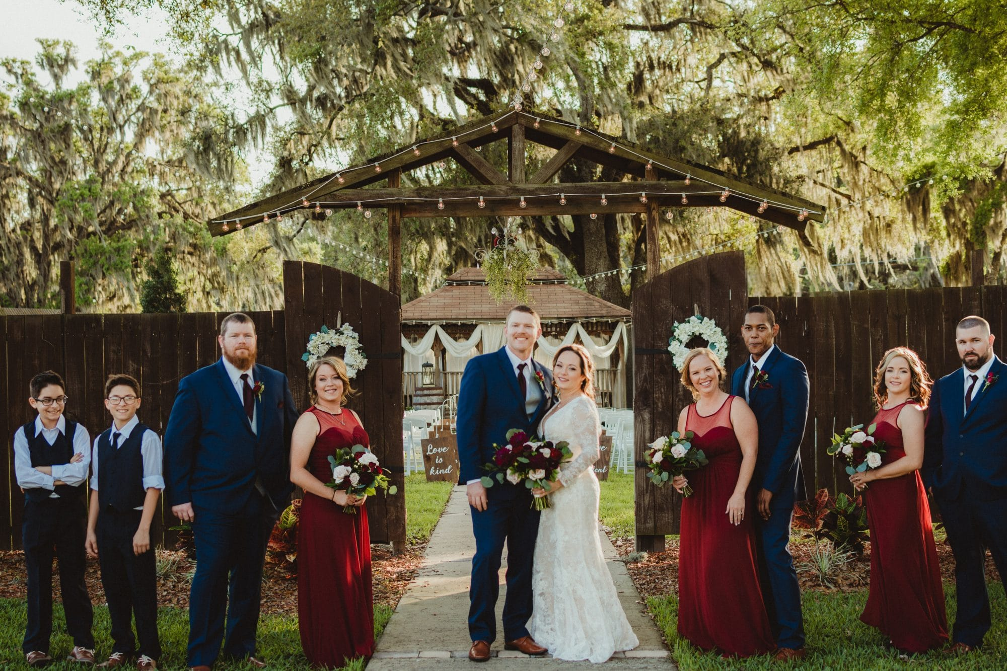 Harmony Haven Event Venue - wedding party in front of rustic wooden gate