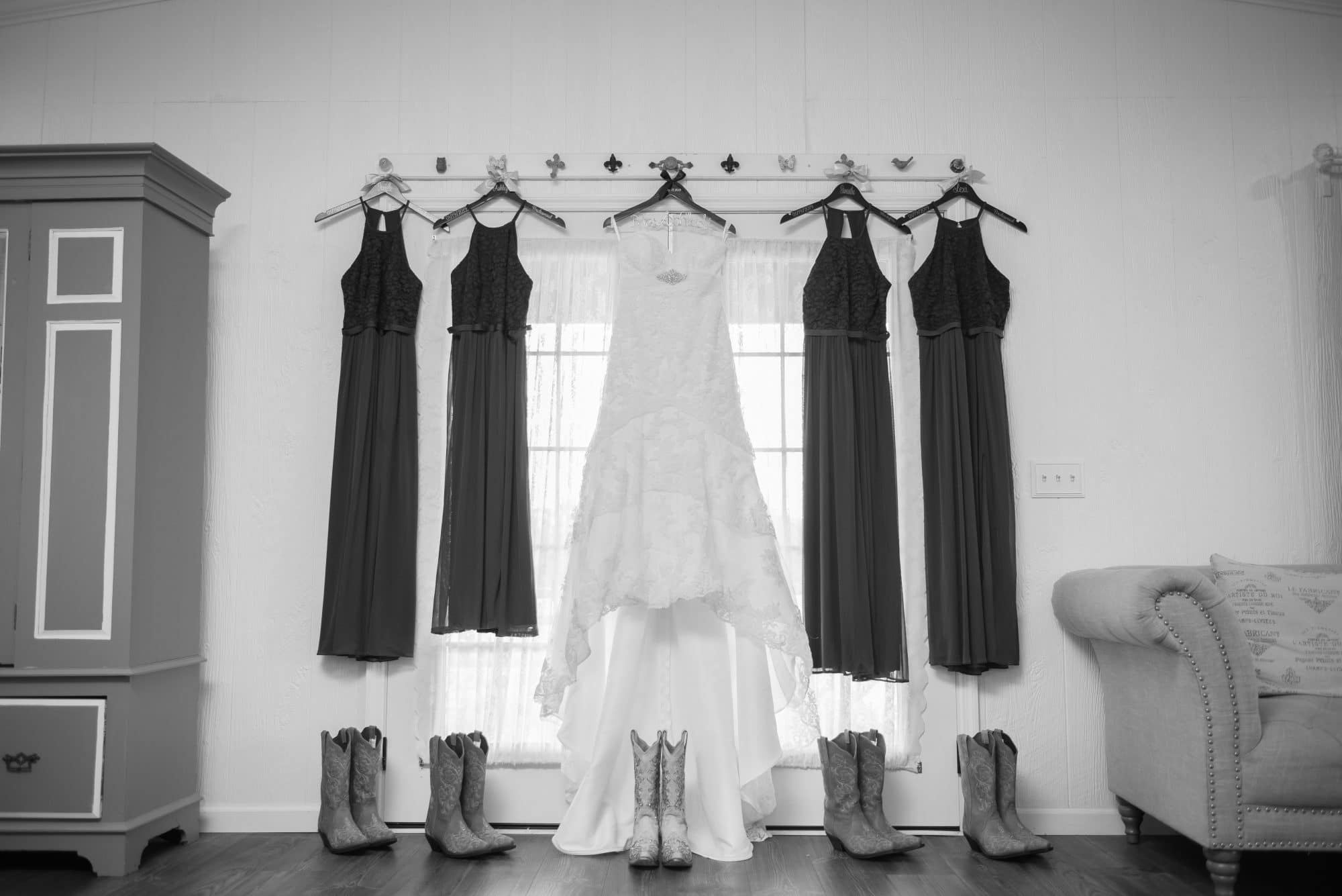 bride and bridesmaids' dresses hung in front of window with cowboy boots underneath