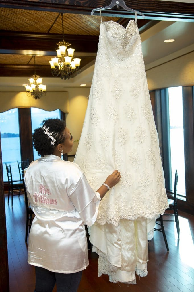 Shaneika in white robe looking at hanging wedding dress