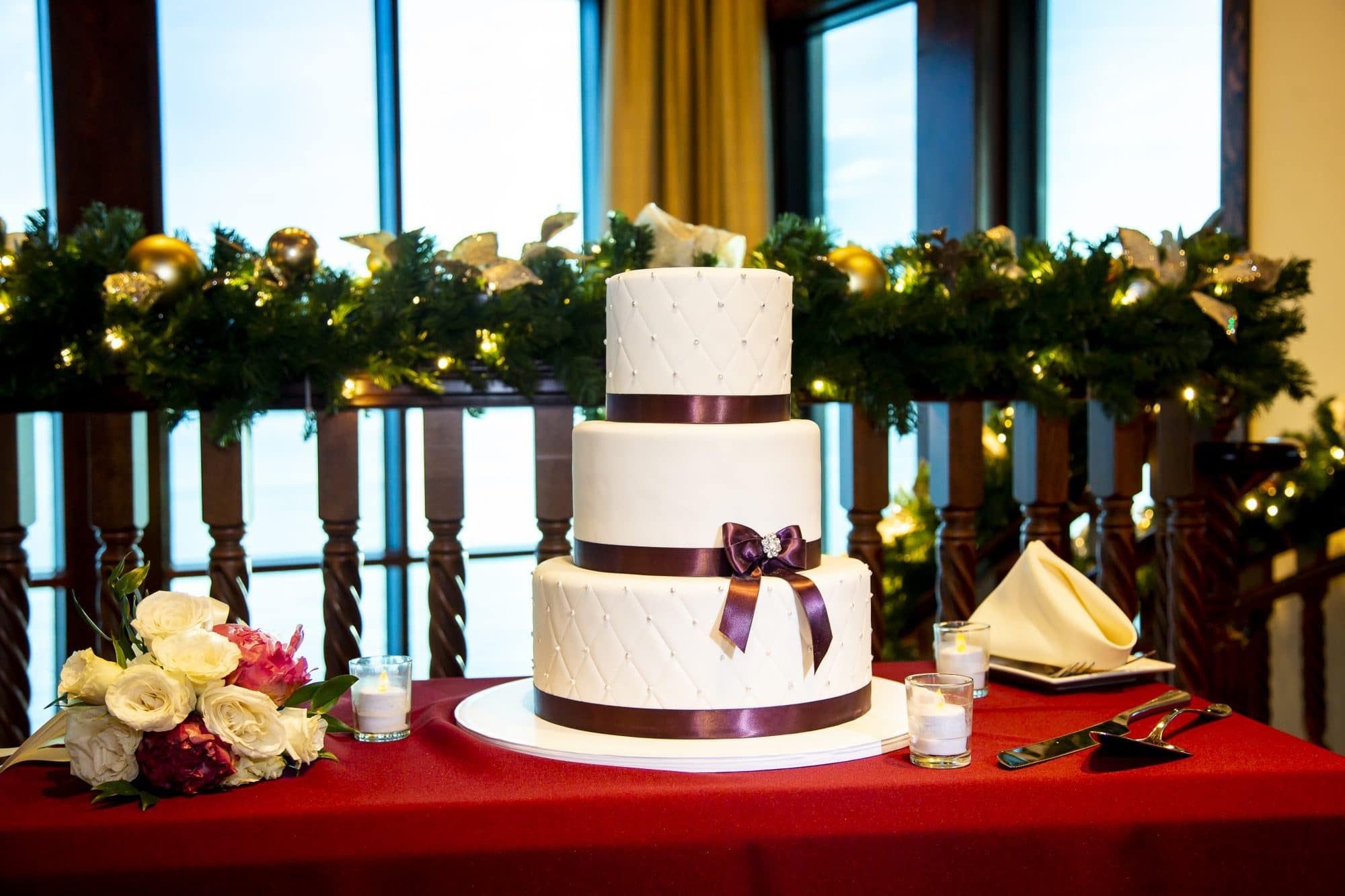 White wedding cake with purple ribbons backed by Christmas decorations