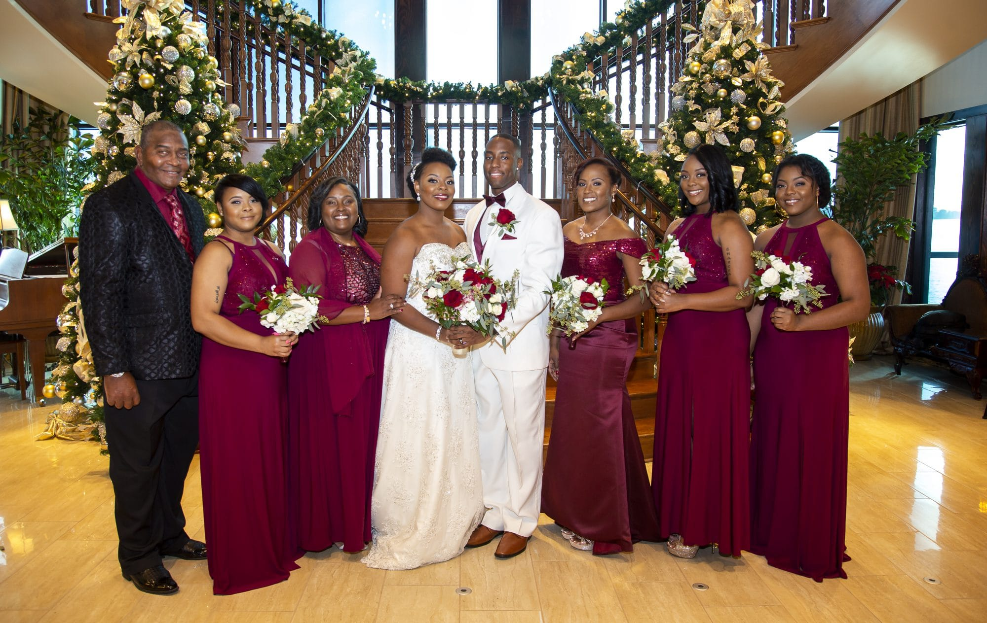 Bride and groom with wedding party in front of gorgeous staircase
