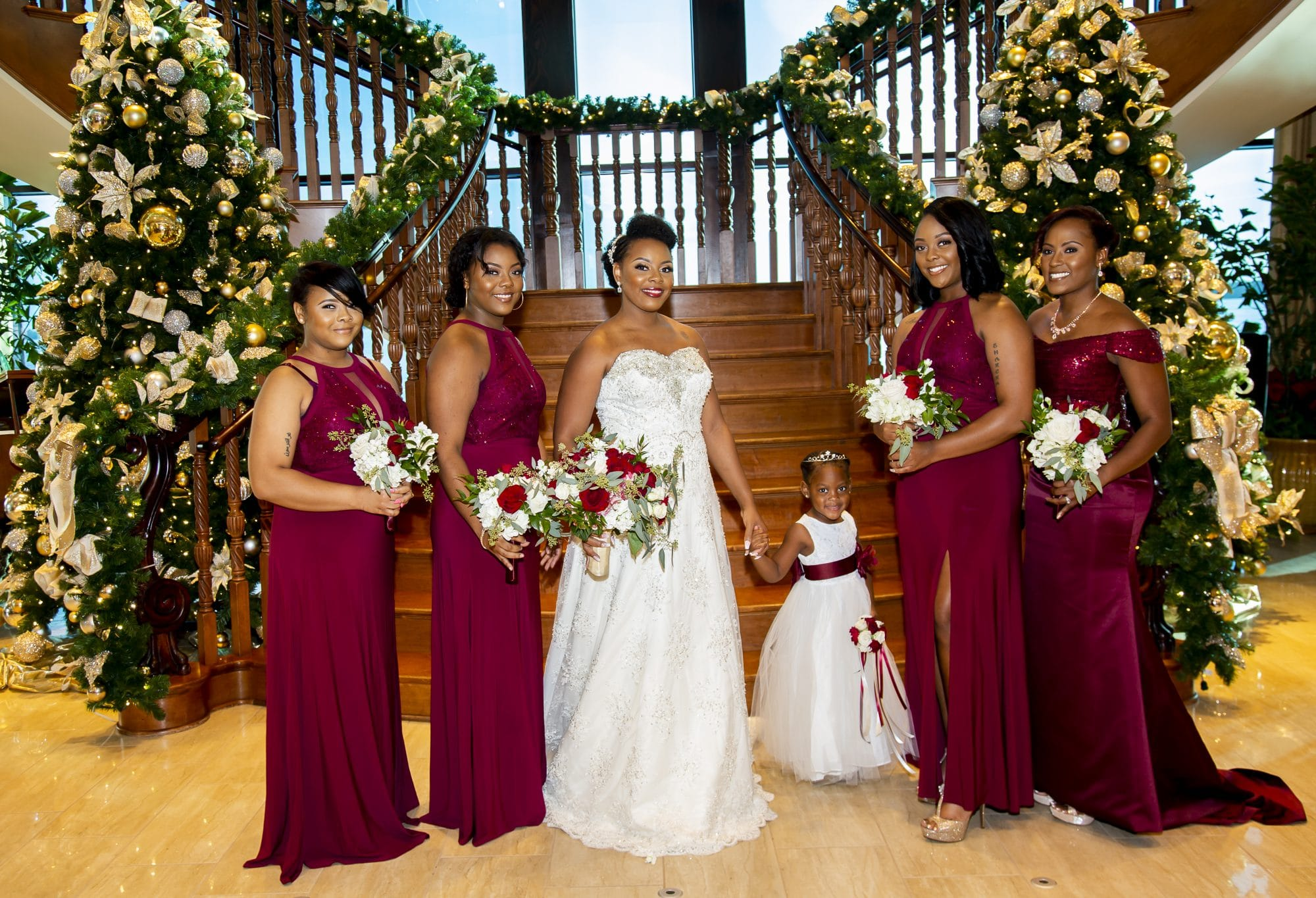 Shaneika with bridesmaids and flower girl in front of sweeping staircase