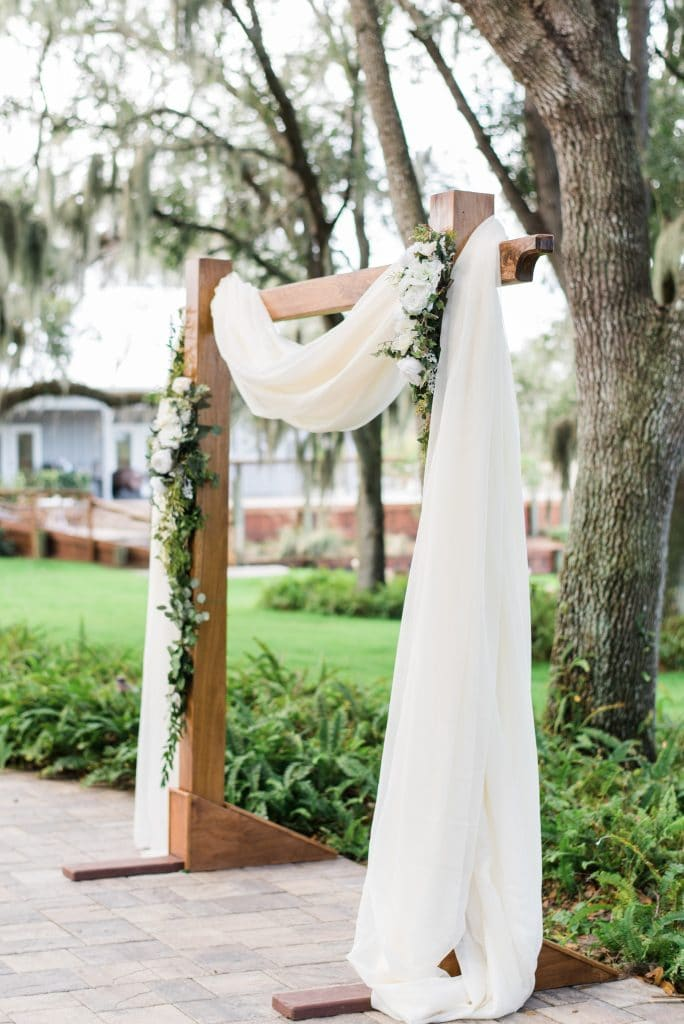 Wooden archway draped with white fabric