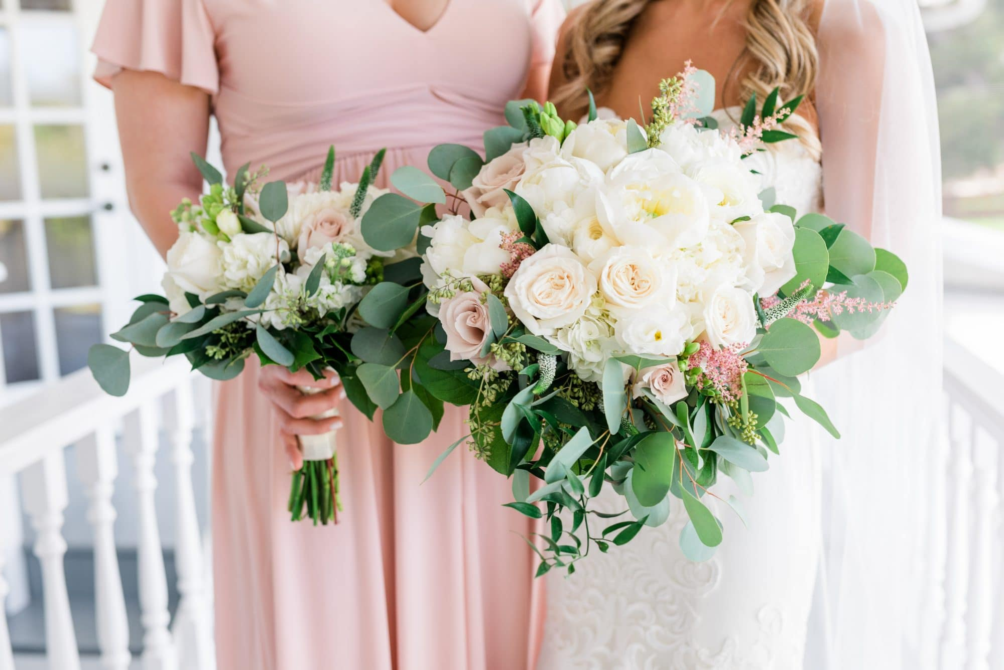 Bride and bridesmaid holding bouquets together