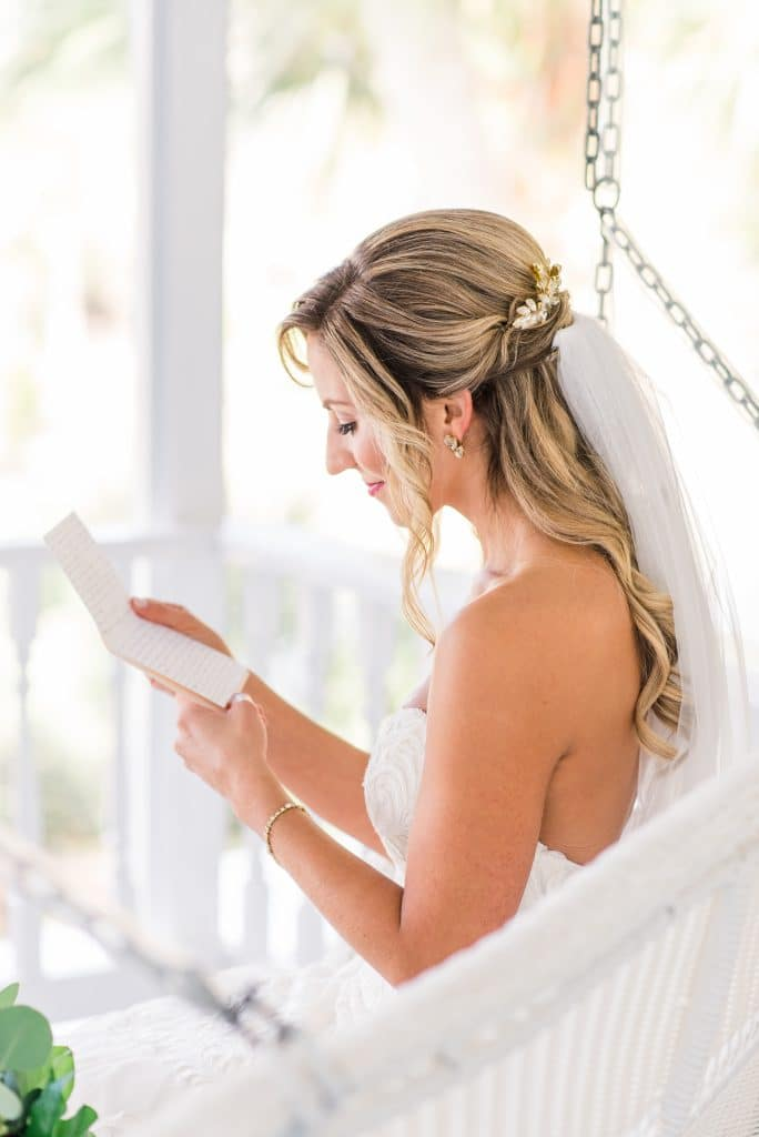 Bride on porch swing reading letter.