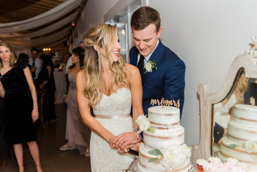 bride and groom slicing semi-naked cake