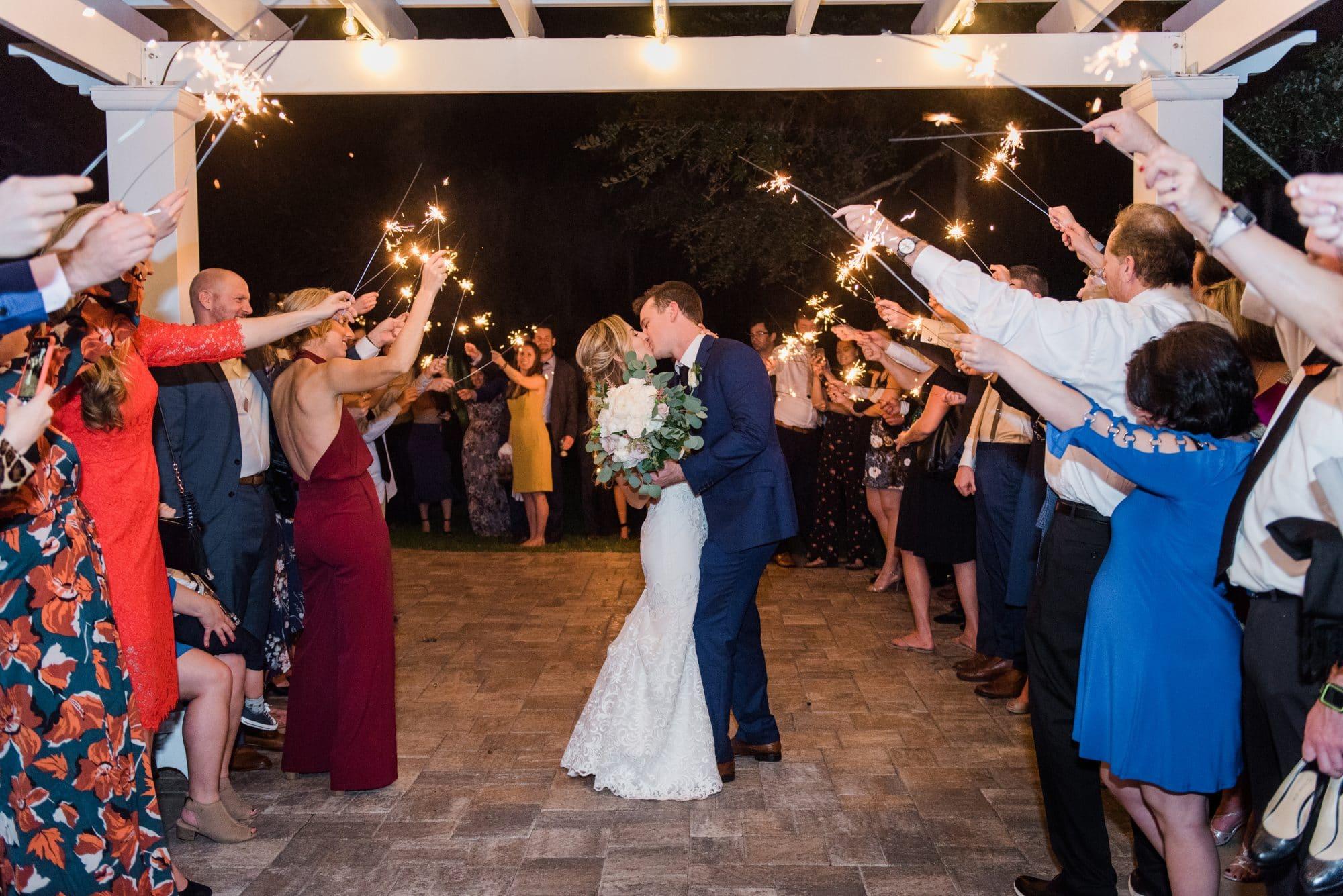 bride and groom kissing under pergola during sparkler sendoff.