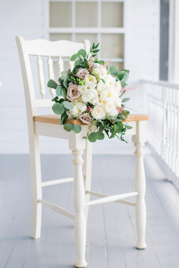 Bride's bouquet sitting on chair on porch