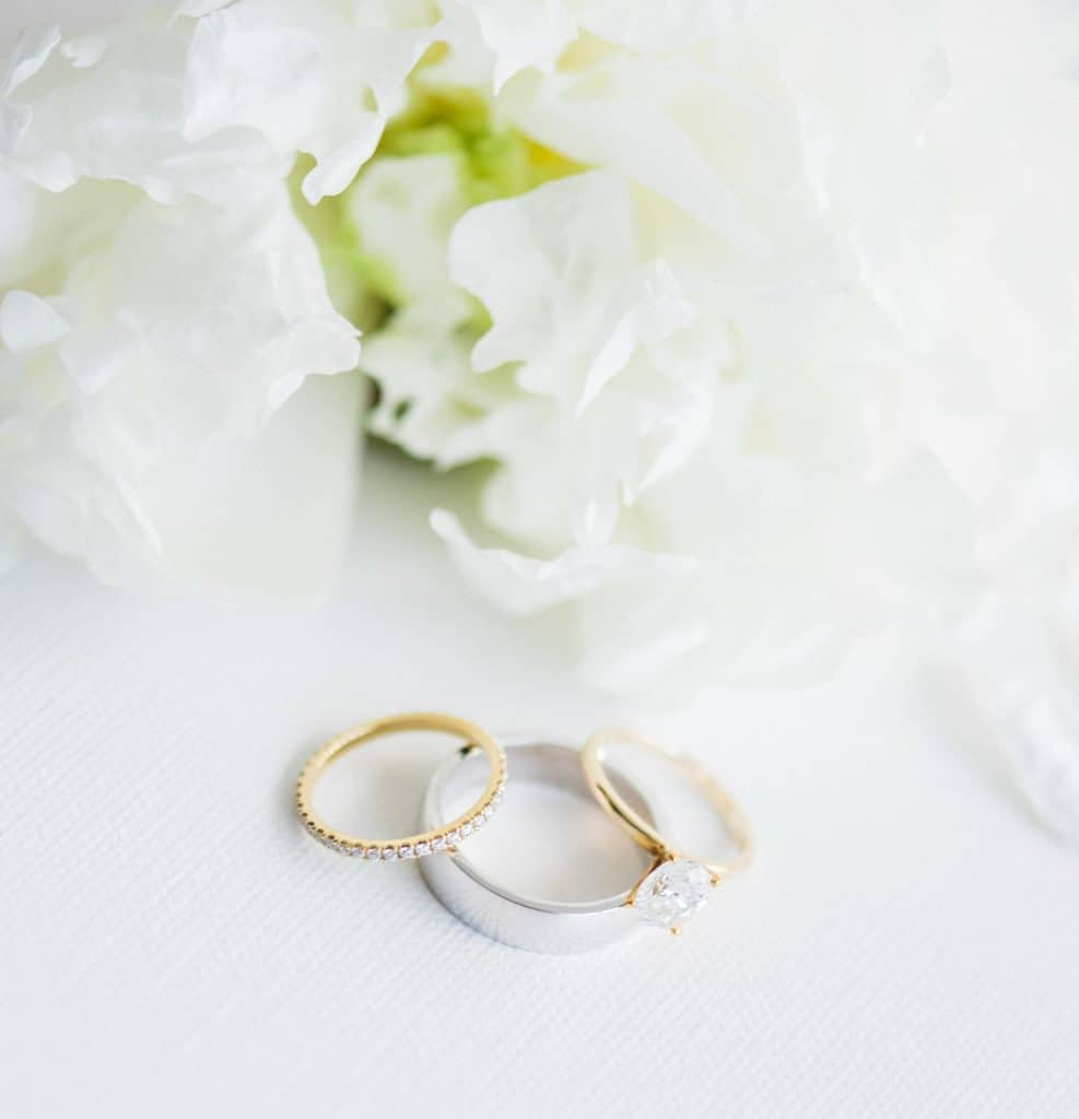wedding rings laid out next to bouquet