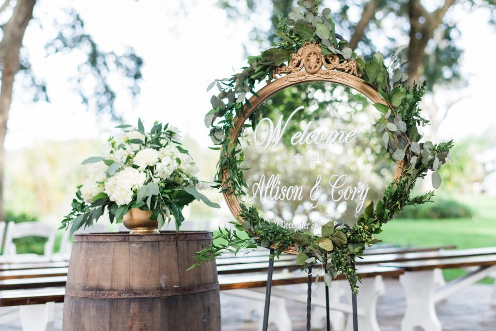 Welcome sign on mirror at outdoor wedding ceremony