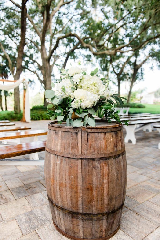 floral arrangement on top of barrel at outdoor wedding ceremony